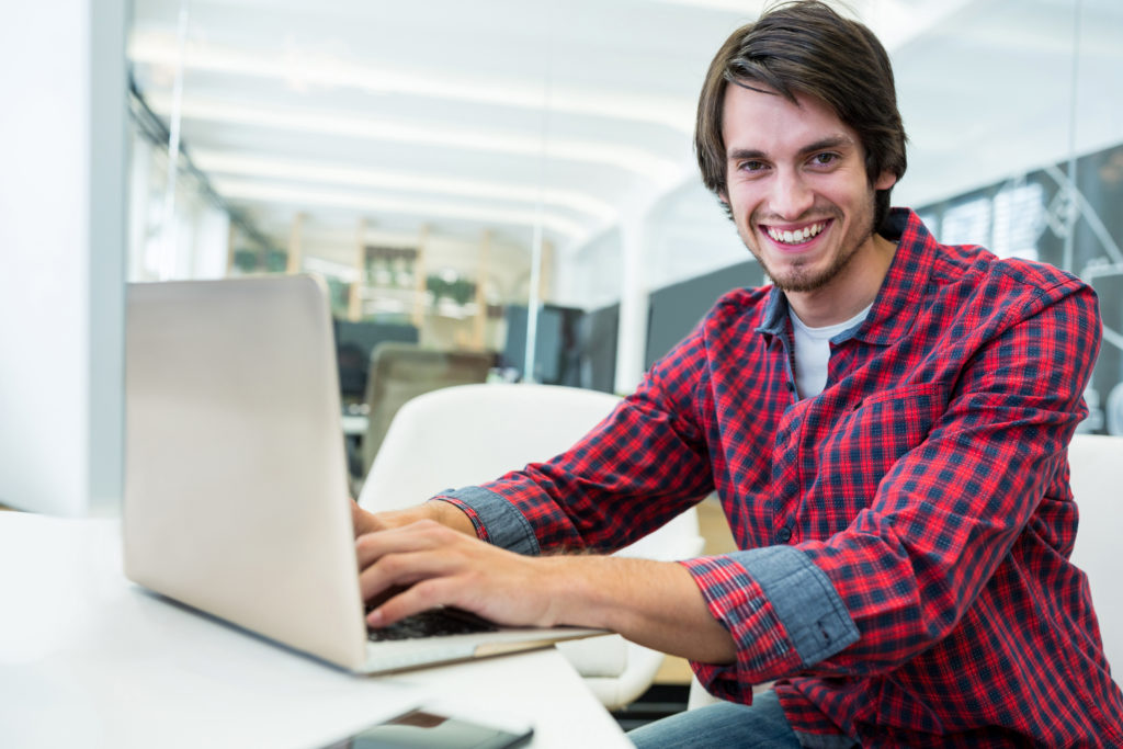 Male business executive using laptop in office